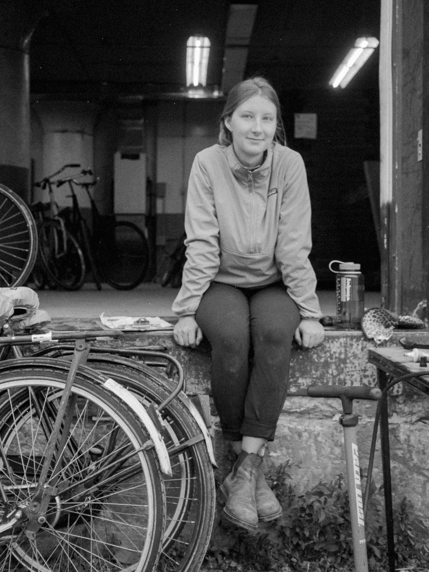 Jenny sitting surrounded by bikes
