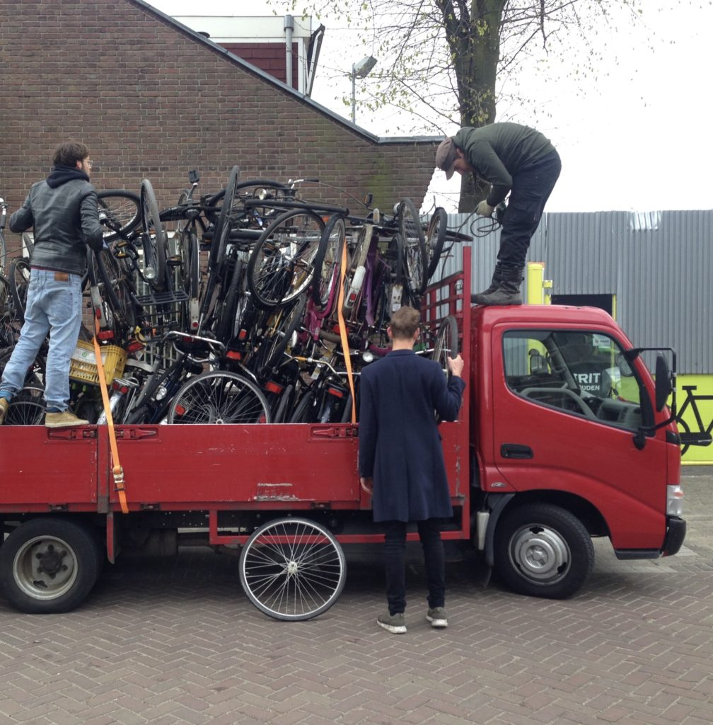 People unloading bicycles from red truck